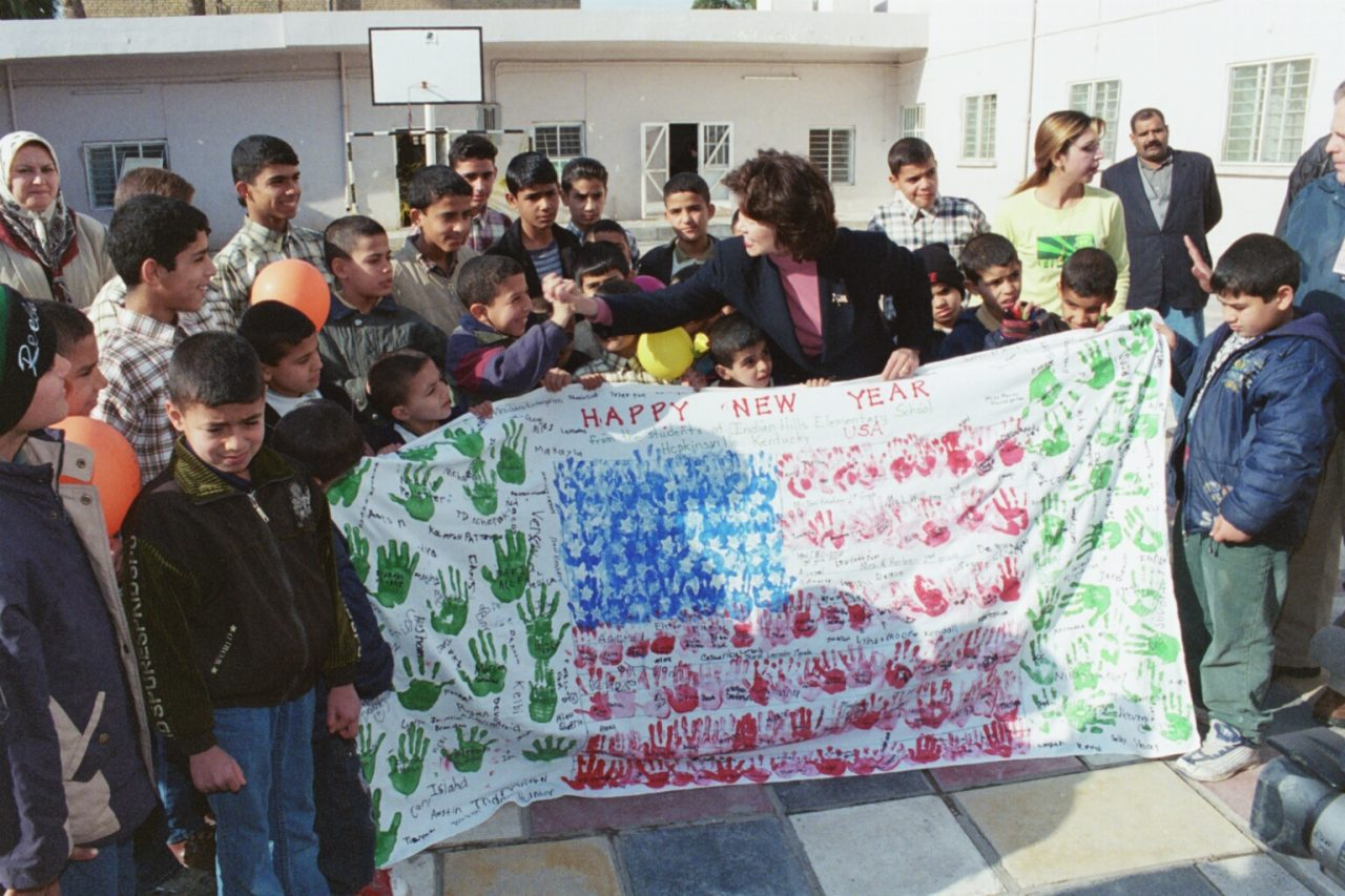 Secretary Elaine Chao visiting an orphanage in Baghdad and bringing a banner made by children at  the Indian Hills Elementary School, Hopkinsville, Kentucky.