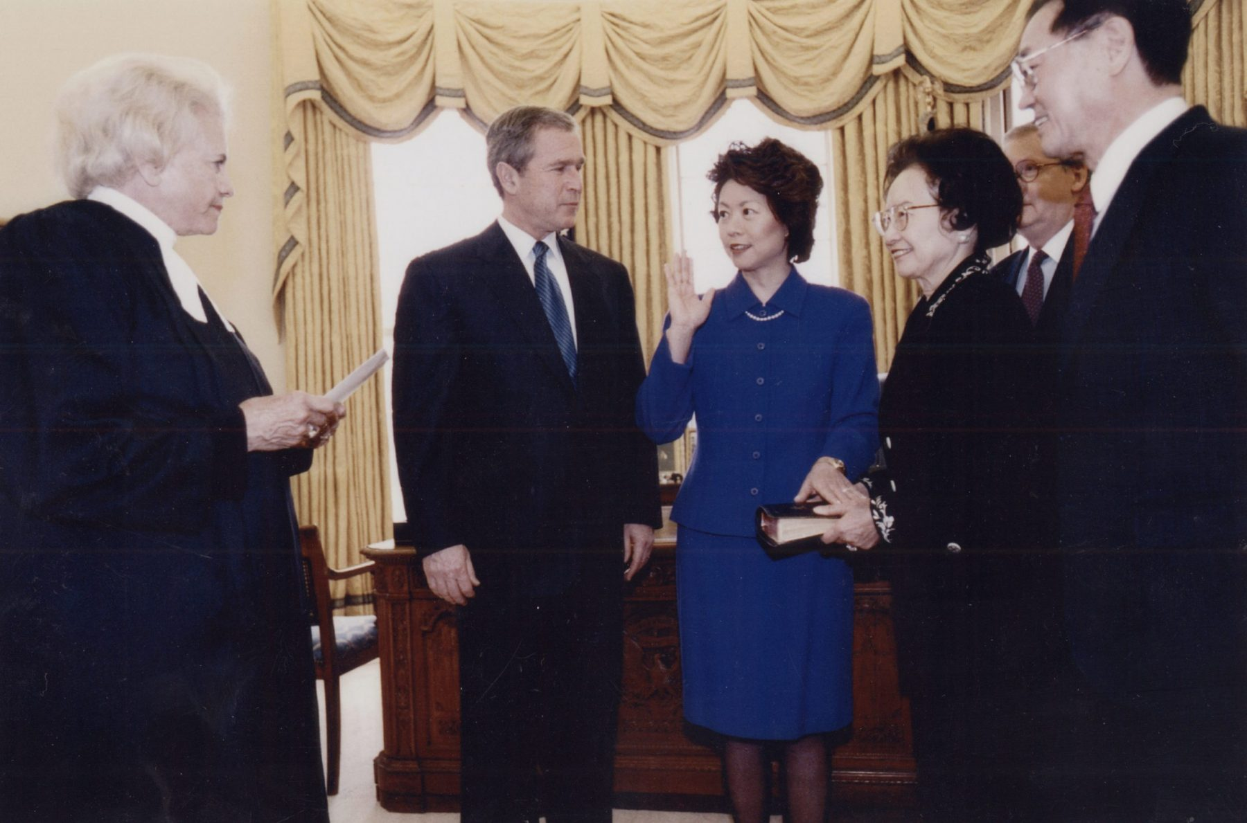 In the Oval Office. Justice Sandra Day O'Connor swearing in Elaine Chao as Secretary of Labor with President George W. Bush; parents, Dr. James S. C. Chao, Mrs. Ruth Mulan Chu Chao; and husband Mitch McConnell looking on.