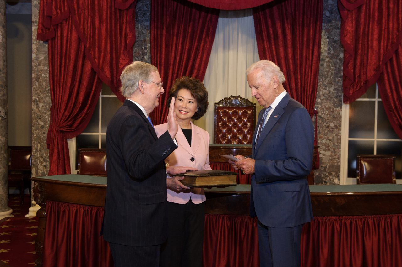 Elaine Chao holds the Bible for husband, U.S. Senate Majority Leader Mitch McConnell as he's sworn in by Vice President Biden at the U.S. Capitol.